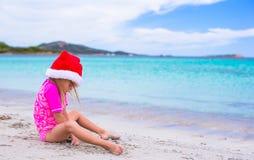 Petite fille adorable dans le chapeau rouge de Santa à tropical Image libre de droits