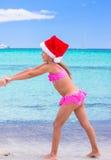 Petite fille adorable dans le chapeau rouge de Santa à tropical Images stock