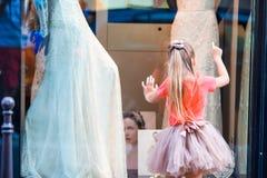 Petite fille adorable dehors dans la ville de l'amour observant de belles robes de mariage Images stock