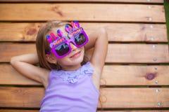 Petite fille adorable en verres de joyeux anniversaire Image stock