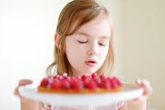 Petite fille adorable et un gâteau de framboise Photos stock