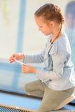 Petite fille adorable jouant avec le petit avion modèle dans l'embarquement de attente d'aéroport Photo libre de droits
