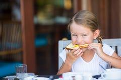 Petite fille adorable mangeant du pain avec du beurre et photos stock