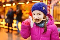 Petite fille adorable mangeant la gaufre couverte de glaçage de chocolat sur le marché traditionnel de Noël Image stock