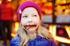 Petite fille adorable mangeant la gaufre couverte de glaçage de chocolat sur le marché traditionnel de Noël Images libres de droits