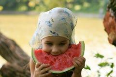 Petite fille adorable mangeant la pastèque Photo stock
