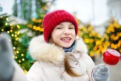 Petite fille adorable mangeant la pomme rouge couverte de glaçage de sucre sur le marché traditionnel de Noël Images stock