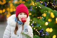 Petite fille adorable mangeant la pomme rouge couverte de glaçage de sucre sur le marché traditionnel de Noël Photo stock