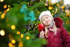 Petite fille adorable mangeant la pomme rouge couverte de glaçage de sucre sur le marché traditionnel de Noël Photos libres de droits