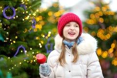 Petite fille adorable mangeant la pomme rouge couverte de glaçage de sucre sur le marché traditionnel de Noël Photo libre de droits