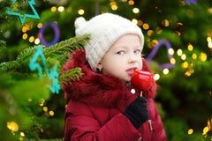 Petite fille adorable mangeant la pomme rouge couverte de glaçage de sucre sur le marché traditionnel de Noël Photographie stock libre de droits