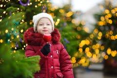 Petite fille adorable mangeant la pomme rouge couverte de glaçage de sucre sur le marché traditionnel de Noël Photographie stock