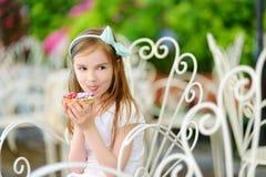 Petite fille adorable mangeant le gâteau doux frais de fraise dehors le jour chaud et ensoleillé d'été Images libres de droits