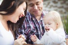 Petite fille adorable mangeant un biscuit avec la maman et le papa Images libres de droits