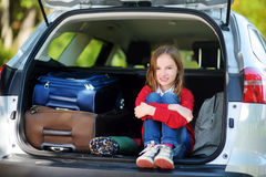 Petite fille adorable prête à partir en vacances avec ses parents Badinez la détente dans une voiture avant un voyage par la rout Photographie stock libre de droits