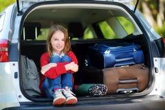 Petite fille adorable prête à partir en vacances avec ses parents Badinez la détente dans une voiture avant un voyage par la rout Images libres de droits