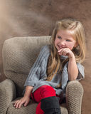 Petite fille adorable riant tout en se reposant dans une chaise Photos stock