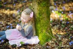 Petite fille adorable sélectionnant les premières fleurs du ressort dans les bois la belle journée de printemps ensoleillée Images libres de droits