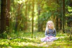 Petite fille adorable sélectionnant les premières fleurs du ressort dans les bois la belle journée de printemps ensoleillée Images stock
