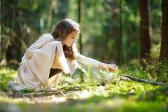 Petite fille adorable sélectionnant les premières fleurs du ressort dans les bois la belle journée de printemps ensoleillée Photos stock