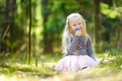 Petite fille adorable sélectionnant les premières fleurs du ressort dans les bois la belle journée de printemps ensoleillée Photos libres de droits