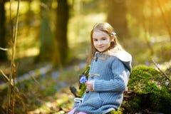 Petite fille adorable sélectionnant les premières fleurs du ressort dans les bois la belle journée de printemps ensoleillée Photo stock