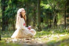 Petite fille adorable sélectionnant les premières fleurs du ressort dans les bois la belle journée de printemps ensoleillée Photo libre de droits