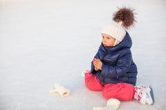 Petite fille adorable s'asseyant sur la glace avec des patins Photos stock