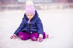 Petite fille adorable s'asseyant sur la glace avec des patins Image stock