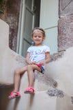 Petite fille adorable s'asseyant sur les étapes de Photo libre de droits