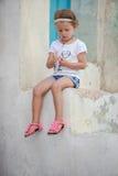 Petite fille adorable s'asseyant sur les étapes de Image stock