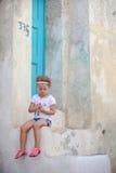 Petite fille adorable s'asseyant sur les étapes de Photo stock