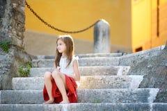 Petite fille adorable s'asseyant sur les escaliers le jour chaud d'été dans la ville de Gargnano en Italie Photographie stock libre de droits