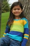 Petite fille adorable se penchant vers le haut contre l'arbre Images libres de droits