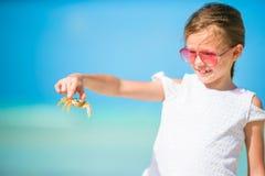 Petite fille adorable tenant le crabe sur la plage Images stock