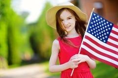 Petite fille adorable tenant le drapeau américain dehors le beau jour d'été Images libres de droits