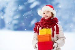 Petite fille adorable utilisant le chapeau de Santa tenant une pile des cadeaux de Noël le beau jour d'hiver Image libre de droits