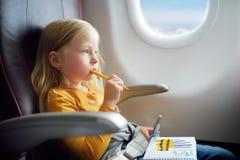 Petite fille adorable voyageant en un avion Enfant s'asseyant par la fenêtre d'avions et dessinant une photo Photo libre de droits