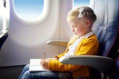 Petite fille adorable voyageant en un avion Enfant s'asseyant par la fenêtre d'avions et dessinant une photo avec les crayons col Image libre de droits