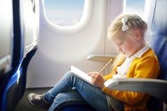 Petite fille adorable voyageant en un avion Enfant s'asseyant par la fenêtre d'avions et dessinant une photo avec les crayons col Images stock