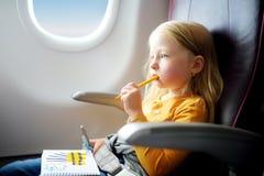 Petite fille adorable voyageant en un avion Enfant s'asseyant par la fenêtre d'avions et dessinant une photo avec les stylos feut Image libre de droits