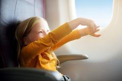 Petite fille adorable voyageant en un avion Enfant s'asseyant par la fenêtre d'avions et regardant dehors Photo libre de droits