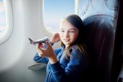 Petite fille adorable voyageant en un avion Enfant s'asseyant par la fenêtre et jouant avec l'avion de jouet Photos libres de droits