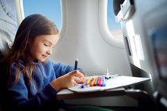 Petite fille adorable voyageant en un avion Enfant s'asseyant par la fenêtre et le dessin Image stock