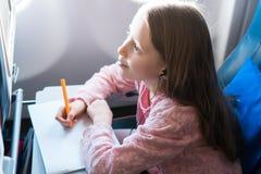 Petite fille adorable voyageant en un avion Photo de dessin d'enfant avec les crayons colorés se reposant près de la fenêtre Photographie stock libre de droits