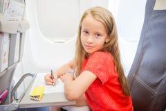 Petite fille adorable voyageant en un avion Photo de dessin d'enfant avec les crayons colorés se reposant près de la fenêtre Photos stock