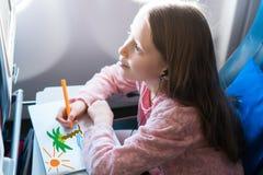 Petite fille adorable voyageant en un avion Photo de dessin d'enfant avec les crayons colorés se reposant près de la fenêtre d'av Photographie stock libre de droits
