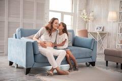 Petite fille affectueuse embrassant sa mère enceinte Photographie stock libre de droits