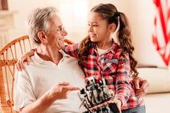 Petite-fille affectueuse et grand-papa parlant au-dessus de la machine robotique Images stock