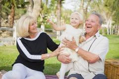 Petite-fille affectueuse et grands-parents jouant au parc Photos libres de droits